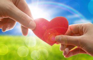 két kéz és szív, műfű a háttérben és kék ég